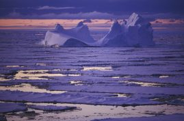 Late light baths an iceberg in pastel colors. Antarctica