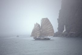 Junk sails through the fog in Ha Long Bay, Vietnam